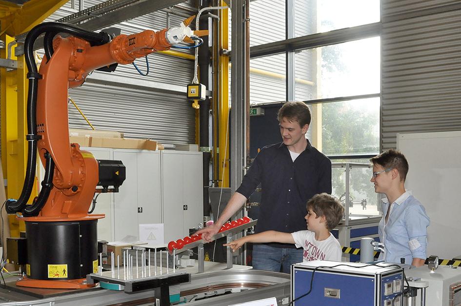 Dieser Roboter kann immerhin schon Bälle sortieren: Johannes bei der Begutachtung zusammen mit Kai Bockwinkel und Ricarda Schmitt.