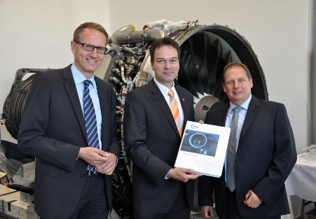 Prof. Jens Friedrichs vom IFAS der TU Braunschweig sowie Alexander Engel und Stephan Rihm von der Firma MTU Maintenance bei der Übergabe des neuen Versuchstriebwerks