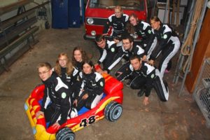 Das BIOMOD-Team als Boxencrew des Nanoscooters in Rennoveralls.