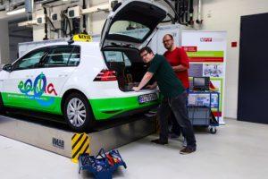 """Die Ingenieure Jonas Wussow und Tim-Hendrik Dietrich arbeiten an der Elektronik, die im Kofferraum des """"emilia""""-Golfs untergebracht ist. (TU Braunschweig), frei zur Veröffentlichung."""