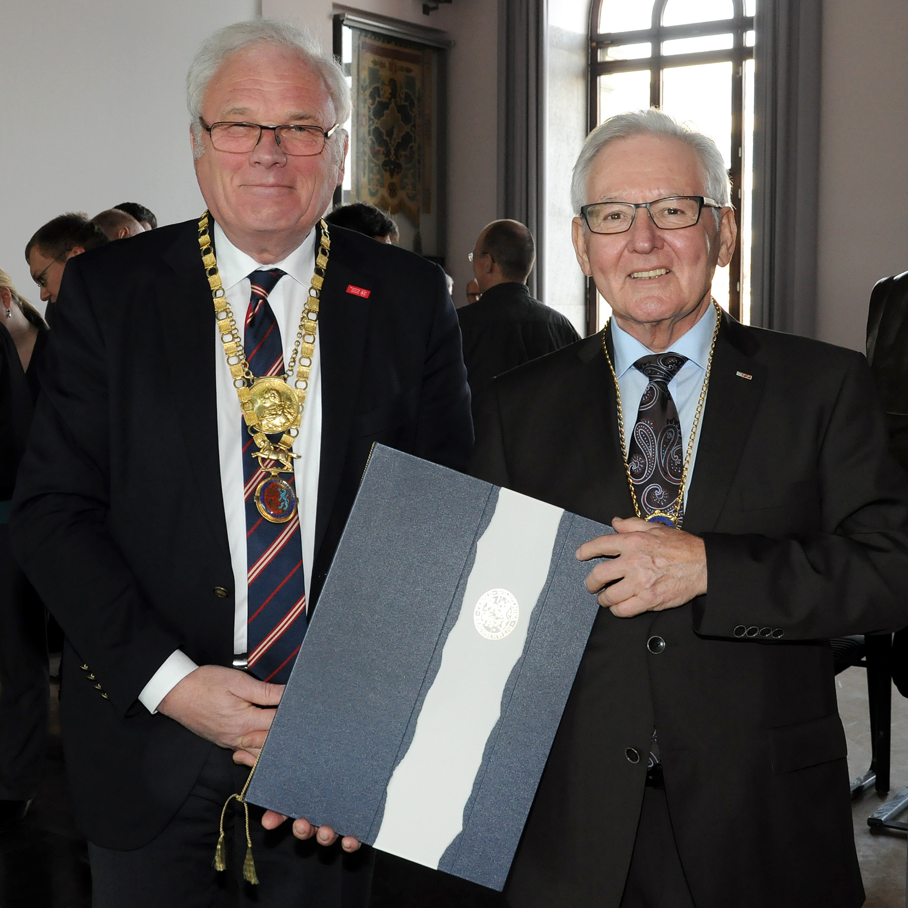 Dr.-Ing. E.h. Kögler (rechts) erhält Urkunde und Amtskette von TU-Präsident Prof. Jürgen Hesselbach.