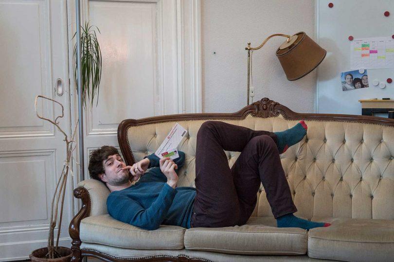 Student Ralph mit Tehaterkarten auf dem Sofa