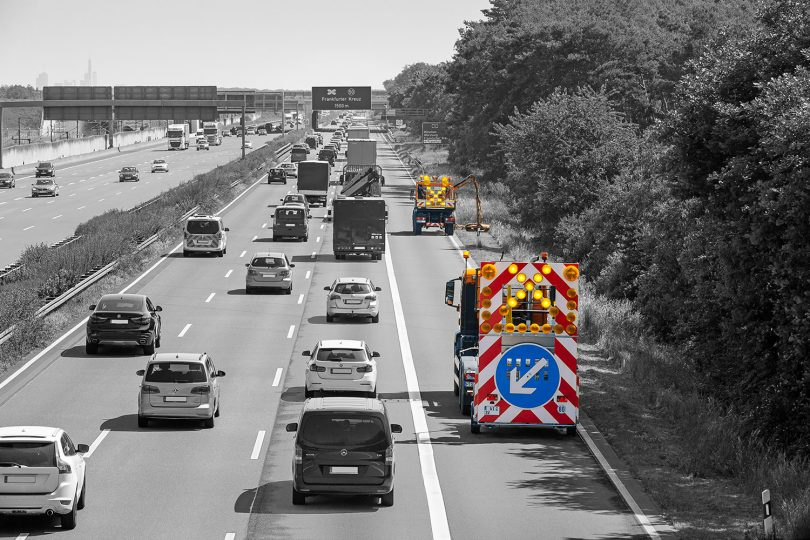 """Schwarz-Weiß-Foto einer befahrenen Autobahn mit farbig hervorgehobenen Baustellenfahrzeugen"""""""