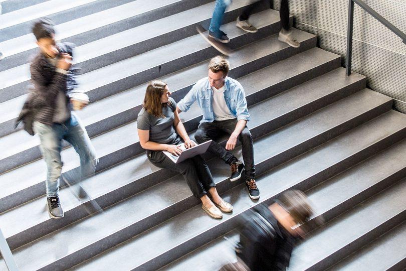 Das Bild zeigt eine Studentin und einen Studenten, auf einer Treppe sitzend, die auf ein Labtop schauen.