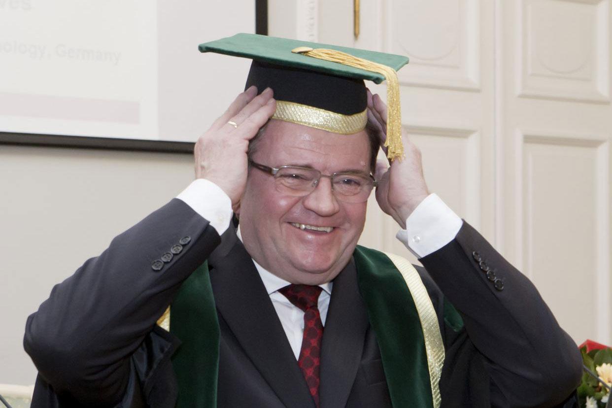 Das Bild zeit Prof. Fritz, der den Doktorhut aufsetzt.