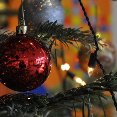 Zwei Weihnachtskugeln hängen an einem Weihnachtsbaum.