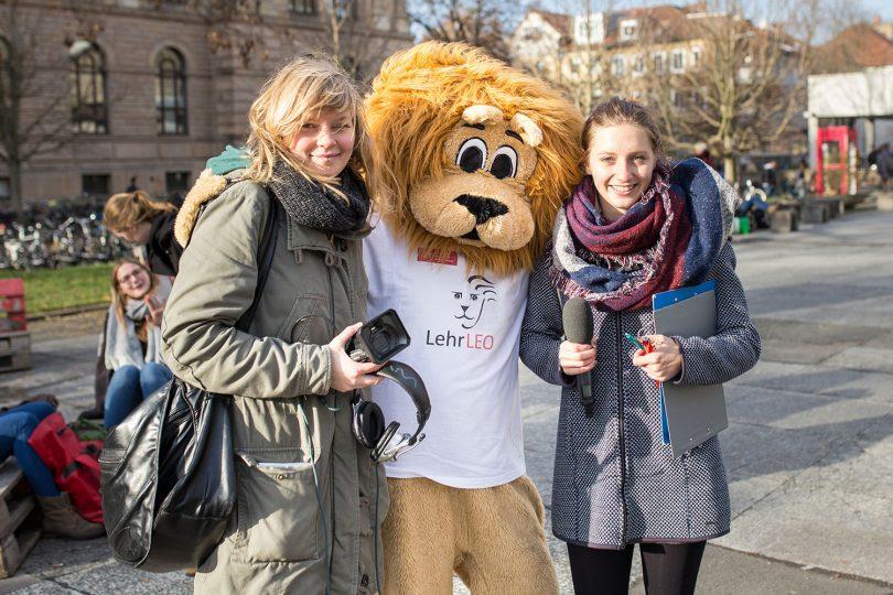Zwei Studentinnen mit dem Maskottchen LehrLEO