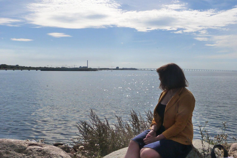 Die Studentin Elisaveta Lebedeva sitzt auf einem Felsen und blickt auf die Öresundbrücke.
