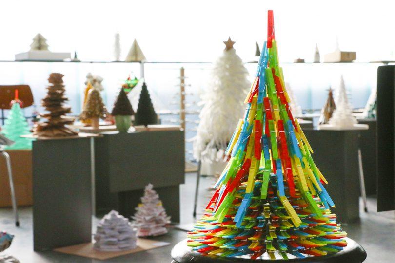 Weihnachtsbaum aus Wäscheklammern, im verschwommenen Hintergrund stehen viele kreative Weihnachtsbaumentwürfe
