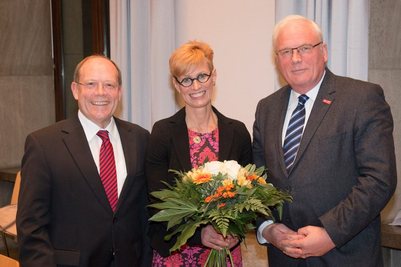 Das Bild zeigt die drei Personen bei der Überreichung eines Blumenstraußes.