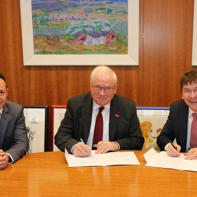 Das Bild zeigt die drei Hauptpersonen bei der Unterzeichnung.