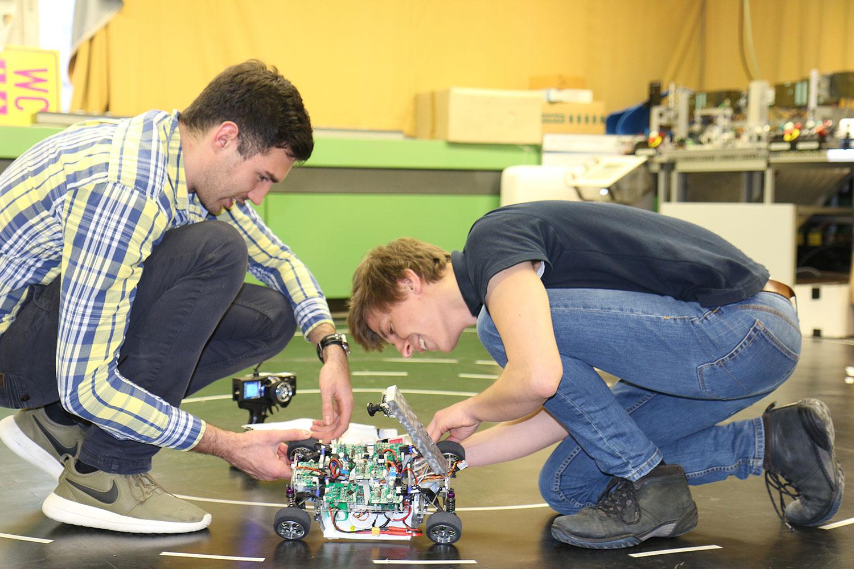 Zwei Mitglieder des Teams CDLC arbeiten am Modellauto.