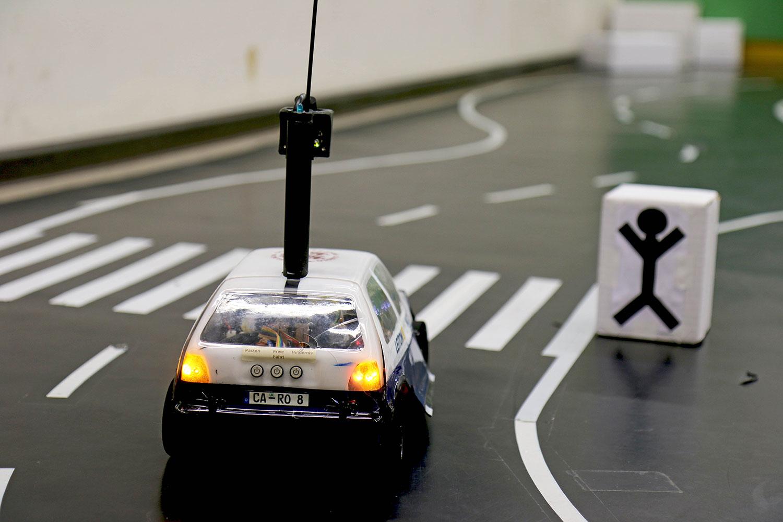 Das Modellauto Carolinchen steht vor einem Zebrastreifen.