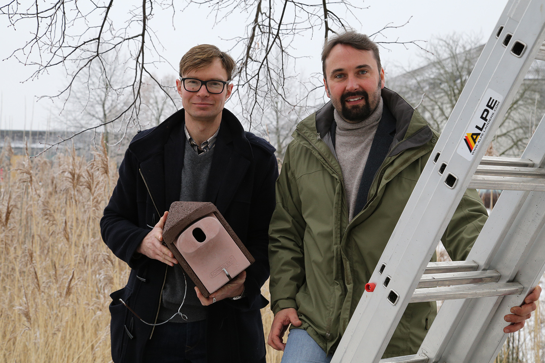 Jan Röhnert und Konstantin Klingenberg stehen mit einer Nisthöhle in der Hand neben einem Baum, an dem die Nisthöhle befestigt werden soll.