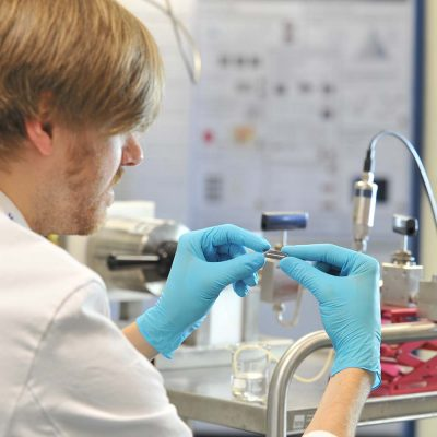 Ein Wissenschaftler prüft Mikrosystem aus Edelstahl.
