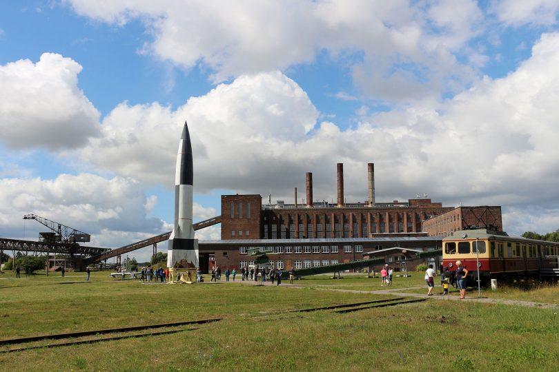 Foto des Außengeländes des Museums in Peenemünde. Eine Rakete und ein Eisenbahnwagon ist zu sehen.