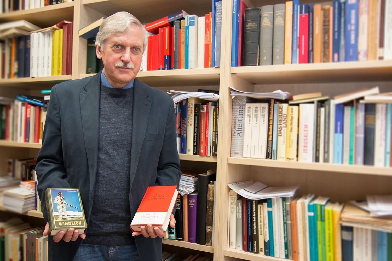 Zu sehen ist Prof. Dr. Jürgen Wehnert, stehend vor einer Bücherwand mit zwei Karl May Romanen in der Hand.