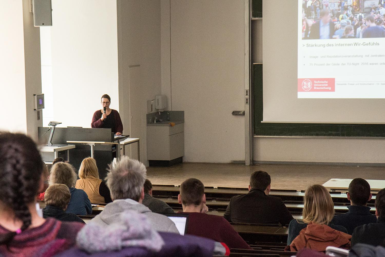 Vorlesungssaal mit Zuhörern von hinten, im Hintergrund spricht Saskia Frank ins Mikro.