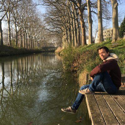Der Student sitzt auf einem Holzsteg an einem Fluss.