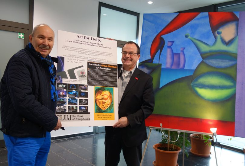 Prof. Jahn und Herr Grove halten ein Plakat hoch.