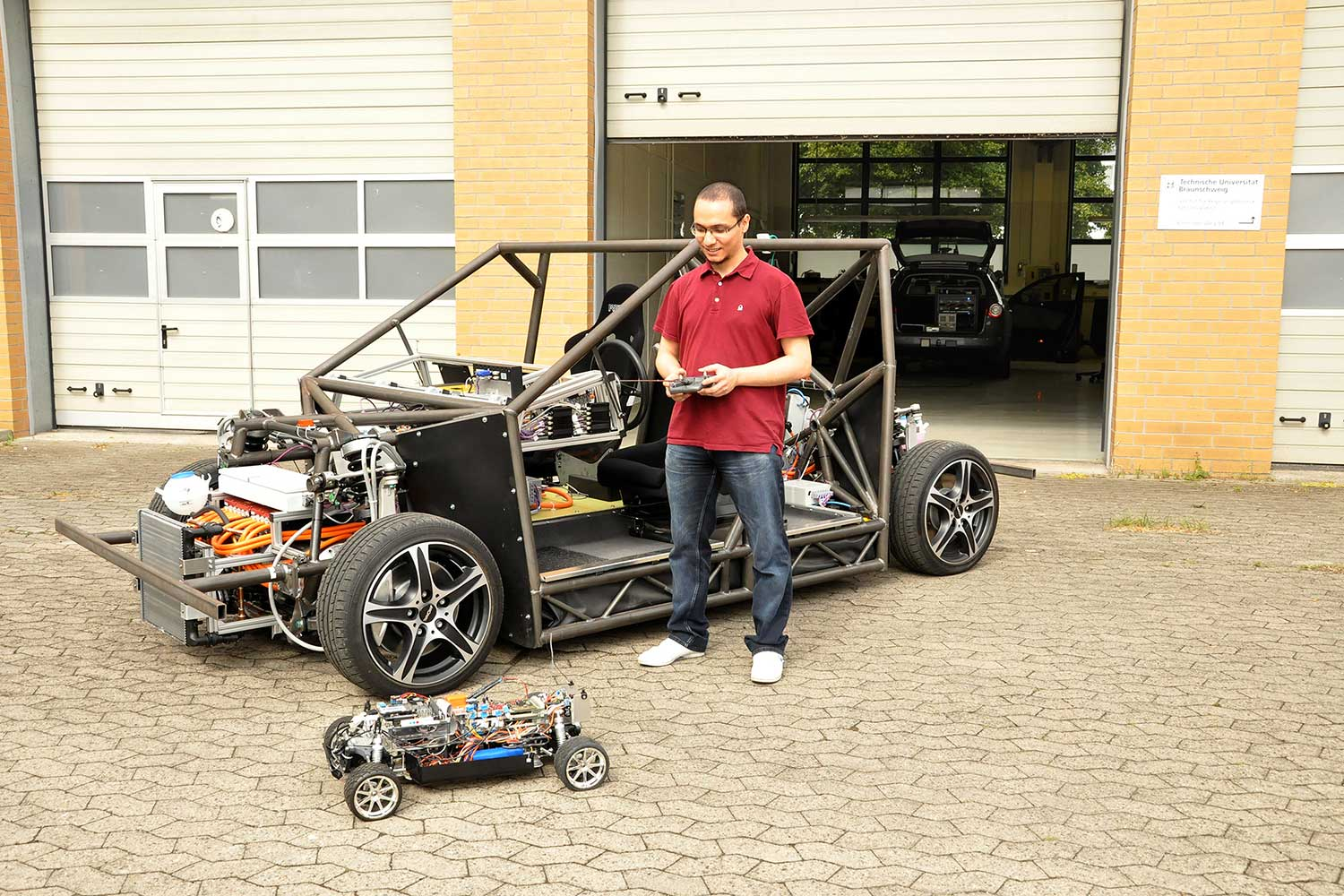 Bashar Ibrahim, student and scholarship holder at the Institute of Control Engineering, compares the size of the MOBILE car to MAX, the practice model at a scale of 1:5. Credit: Kristina Rottig/TU Braunschweig