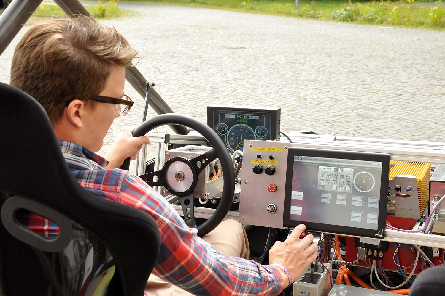 """Monitors instead of a dashboard – the MOBILE vehicle is also transparent inside. Behind the """"steering wheel"""": Torben Stolte. Credit: Kristina Rottig/TU Braunschweig"""