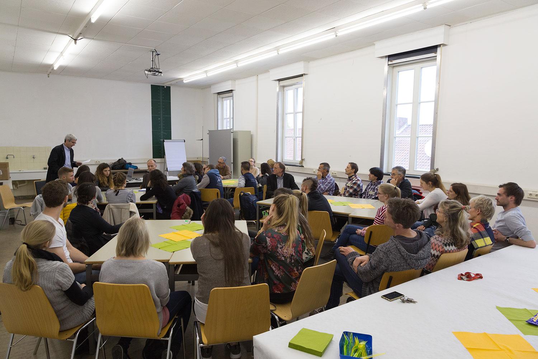 Die Studierenden und Wissenschaftler sitzen an Gruppentischen und hören dem Redner zu.