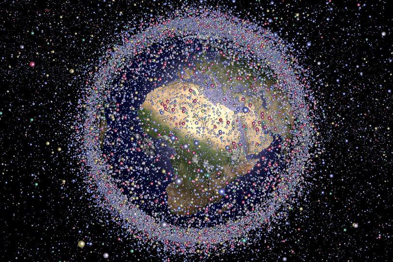 Zu sehen ist ein Modell der Erde, das von vielen kleinen Objekten umgeben ist, die den Weltraummüll darstellen sollen.