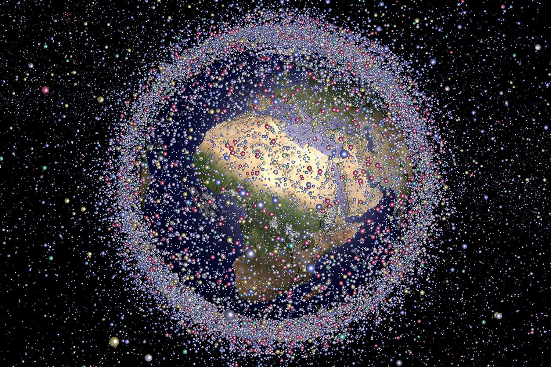 Zu sehen ist ein Modell der Erde, das von vielen kleinen Objekten umgeben ist, die den Weltraumschrott darstellen sollen.