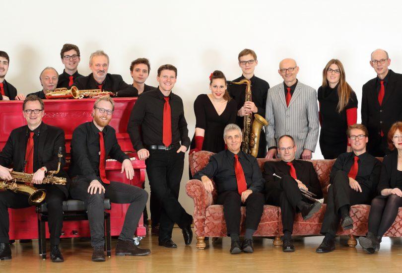 Alle Musikerinnen und Musiker der Bigband um ein rotes Sofa stehend und sitzend.