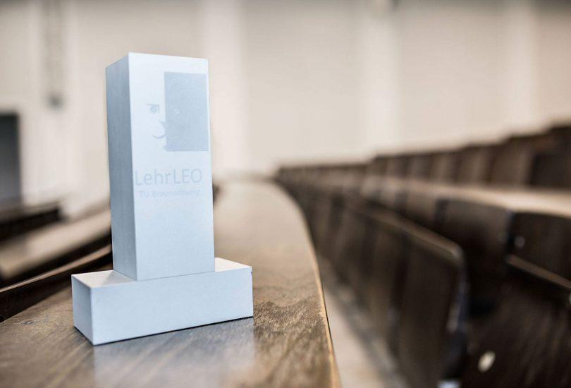 Zu sehen ist die weiße LehrLeo-Trophäe, die auf einem Tisch im Hörsaal steht.