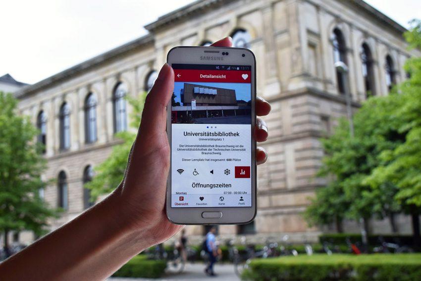 Zu sehen ist ein Handy mit der Startseite der App, das vor das Altgebäude der TU Braunschweig gehalten wird.