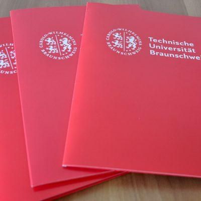 Zu sehen sind drei rote Mappen der TU Braunschweig, die zur Verleihung von Zeugnissen und Urkunden geutzt werden.