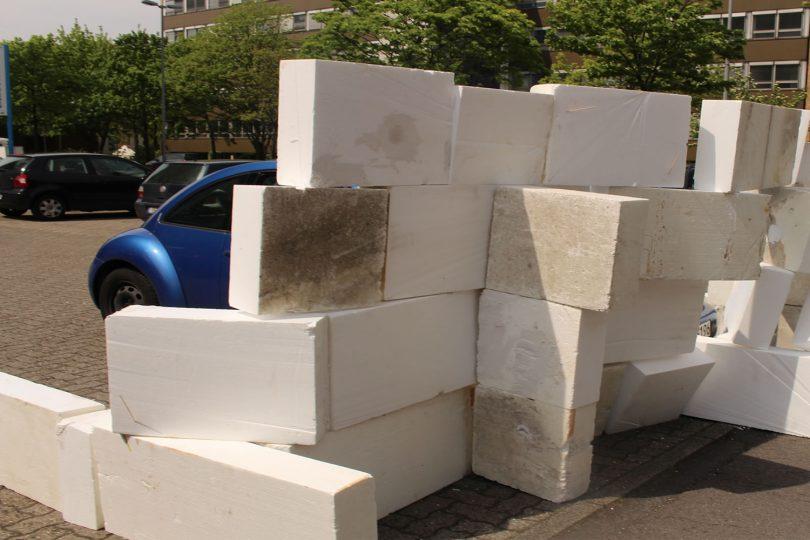 Zu sehen ist ein Teil eines Autos, das in einem Parkplatz, bestehend aus Styropor-Platten, steht.
