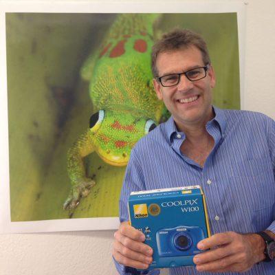 Professor Vences vor seinem Gecko-Bild mit Kamera in den Händen.