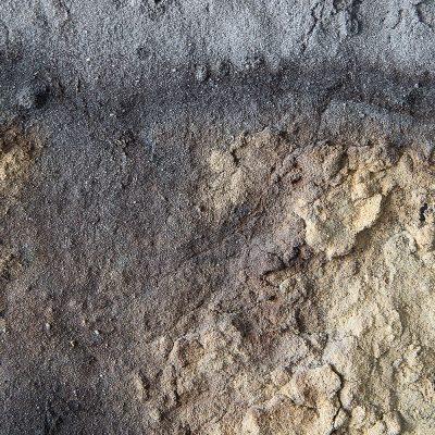 Zu sehen ist ein Bodenprofil, dessen Farben von Schwarz bis hell gelb reichen.