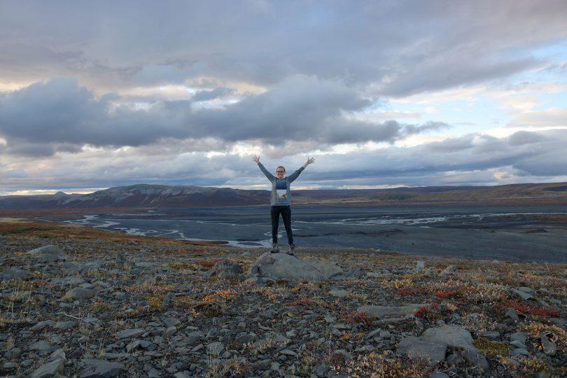 Die Studentin steht auf einem Stein in der isländischen Natur.