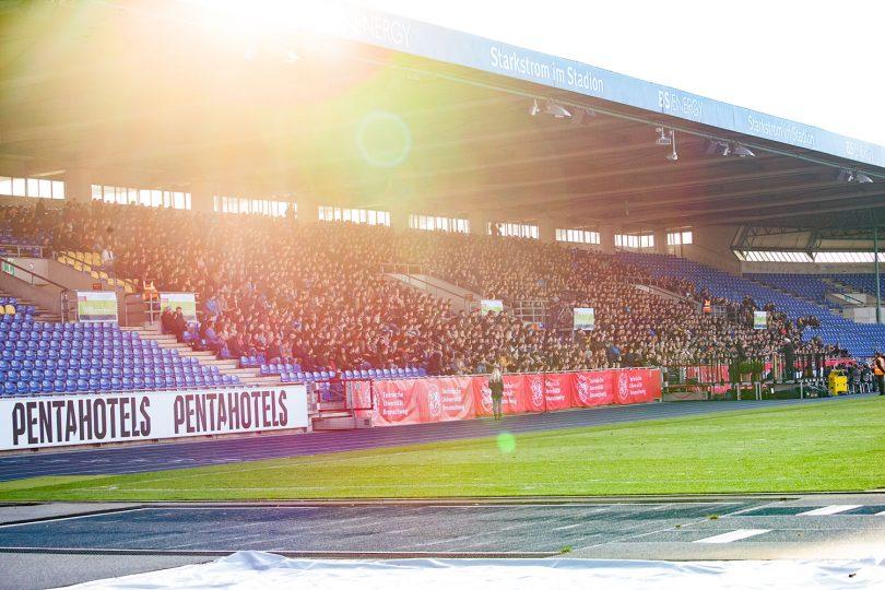 Bild des Eintracht-Stadions (Osttribüne) im Sonnenaufgang.