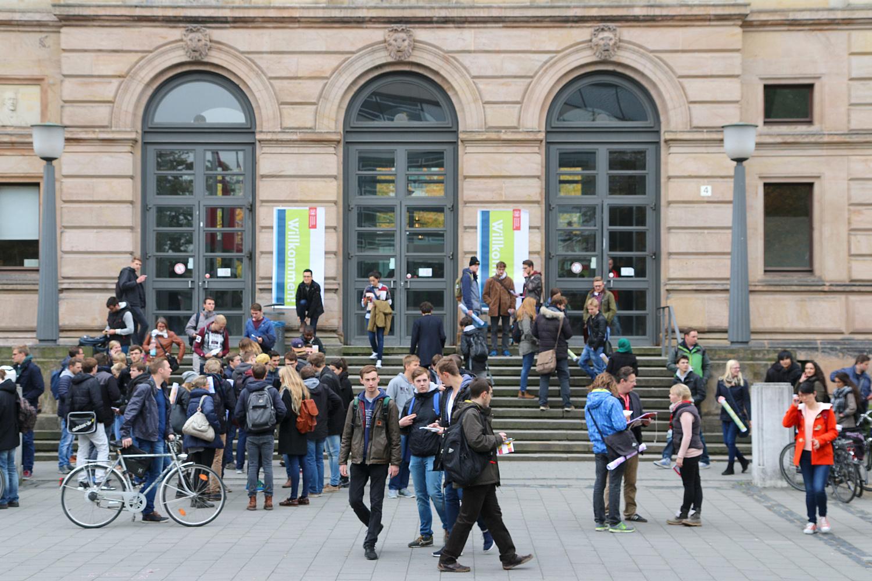Foto vom Haupteingang des Altgebäudes. Viele Studierende sind zu sehen.