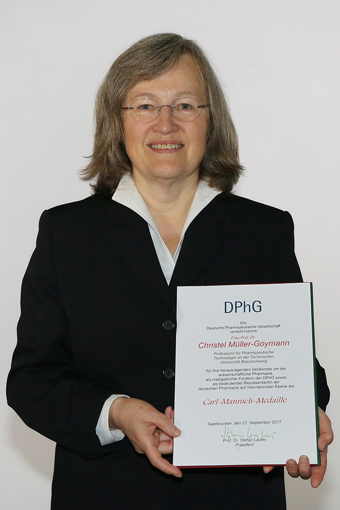Zu sehen ist Prof. Dr. Christel Müller-Goymann im Porträt. In der Hand hält sie eine Urkunde.