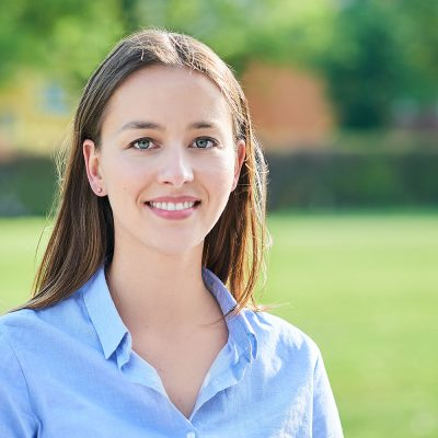 Kopbild von Nora Hartwig mit braunem langen Haar und einer hellblauen Bluse vor grünem unscharfem Hintergrund
