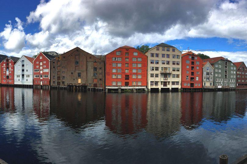 Zu sehen sind bunte Häuser auf Stelzen, die direkt am Ufer eines Flusses stehen.