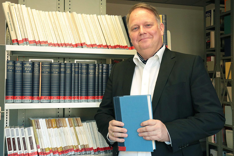 Zu sehen ist Dr. Schnepper in der Bibliothek des Seminars für Evangelische Theologie und Religionspädagogik.