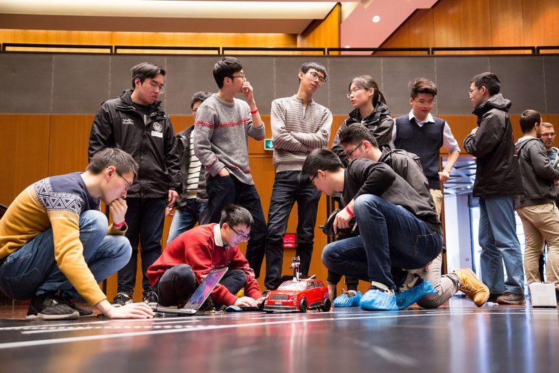 Zu sehen sind die Teammitglieder des chinesischen Teams, die an ihrem Modellfahrzeug arbeiten.