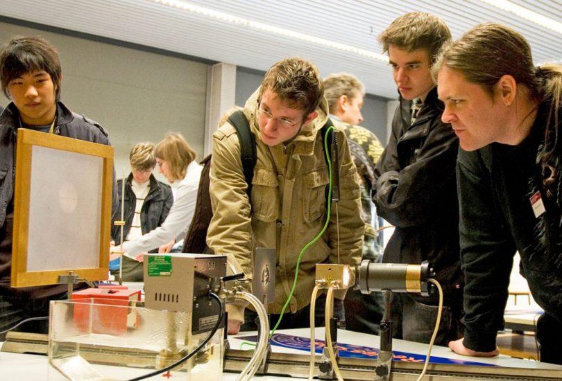 Zu sehen sind Schülerinnen und Schüler, die um einen Versuchsaufbau stehen.