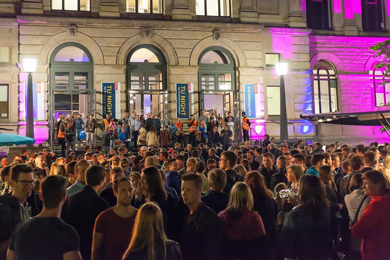 Zu sehen ist das Altgebäude und eine Menschenmenge davor am Abend der TU-Night.
