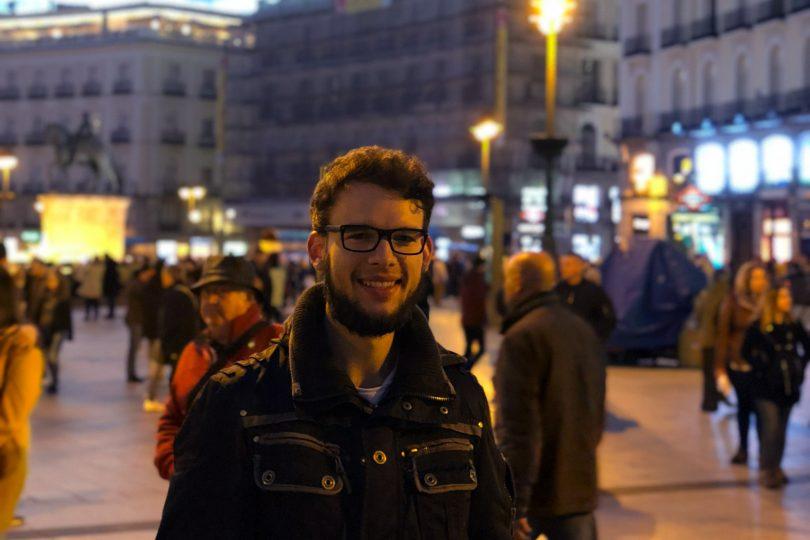"""Zu sehen sind der Student und im Hintergrund der Hauptplatz """"Puerta del Sol""""."""