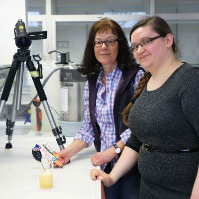 Zu sehen sind Prof. Kerstin Höner und Kristiena Matis zu sehen, die einen Versuch im Chemielabor demonstrieren.