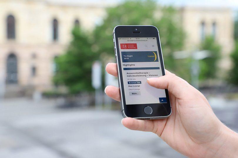 Zu sehen ist ein Smartphone mit der Webseite der TU-Night.