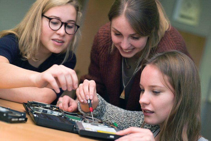 Zu sehen sind drei junge Frauen, die gerade an einem technischen Gerät arbeiten.